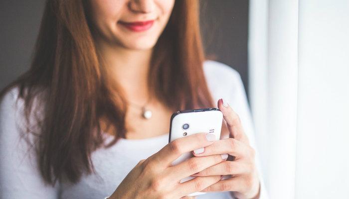 Mulher usando celular para navegar na internet.