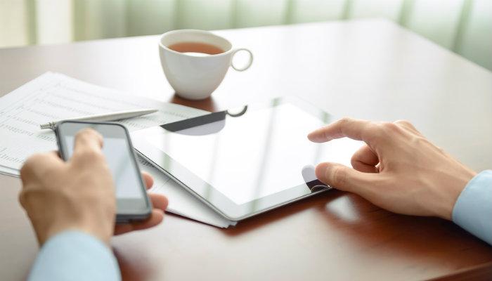 Empreendedor com smartphone e tablet.