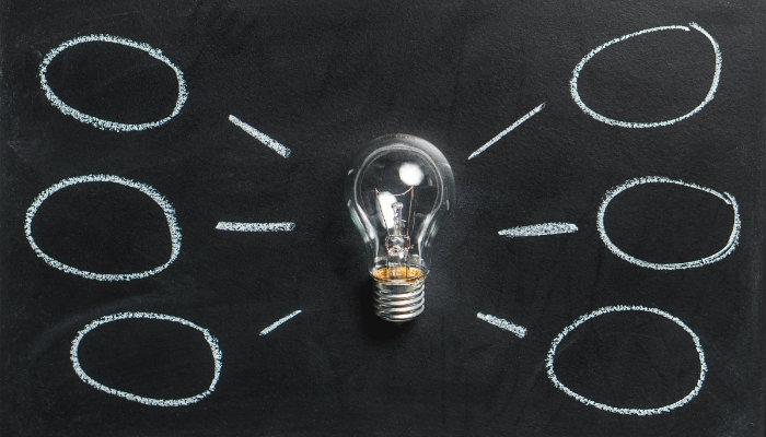 certezas e incertezas lâmpada em cima de um quadro de giz