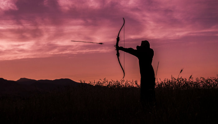 Homem lançando flecha no alvo distante