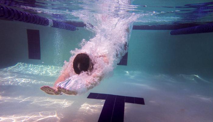 Homem mergulhando em piscina