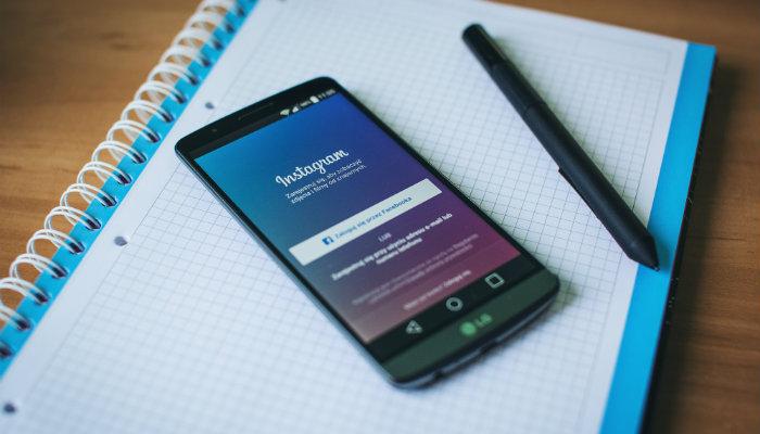 marketing no instagram celular e caneta preta em cima de uma caderno quadriculado