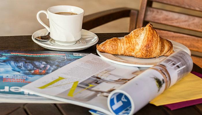 novidades de agosto 2017 xícara de café e revistas na mesa