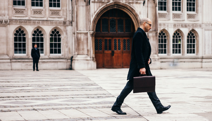 homem demitido caminhando com maleta