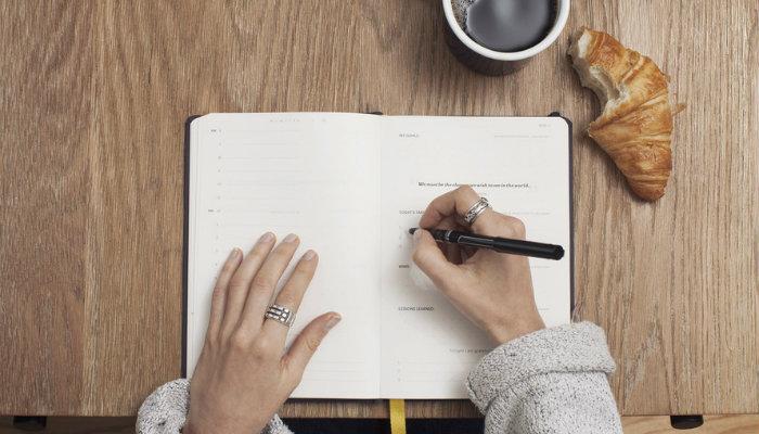 Pessoa escrevendo em agenda