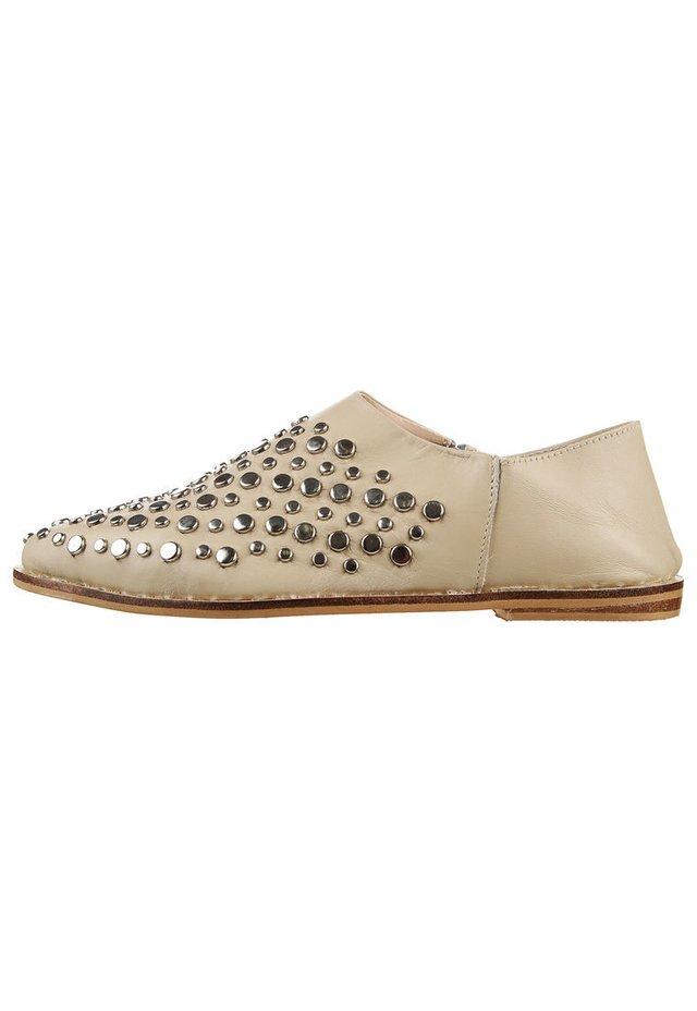 5fbc95c31588a Zapato de cuero natural crudo con tachas
