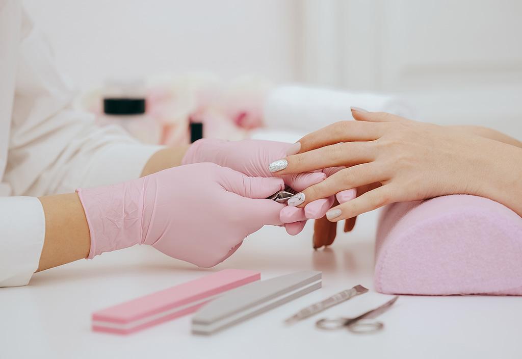 Manicure trabalhando nas unhas de uma cliente