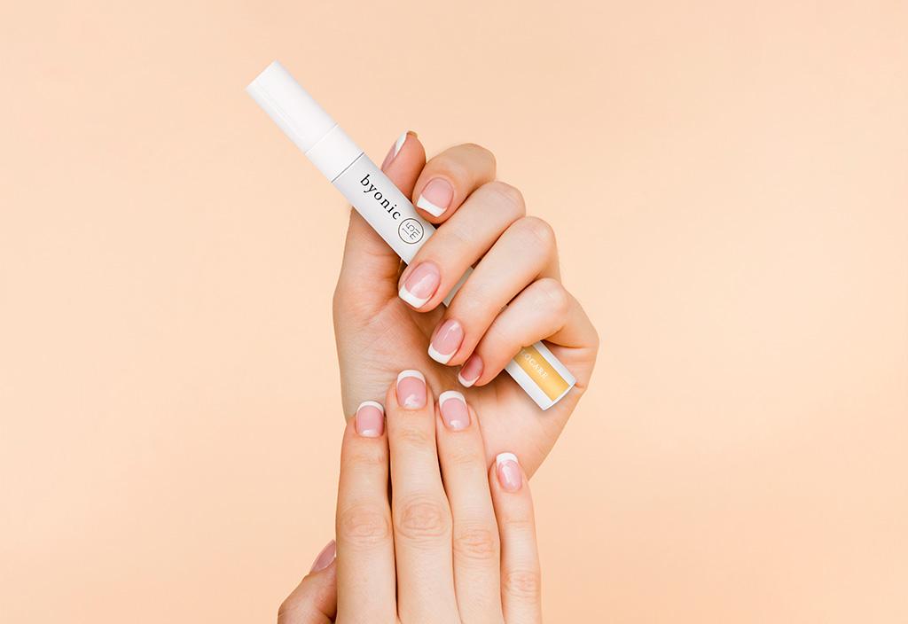 Mão segurando a Byonic, caneta para crescimento e fortalecimento das unhas.